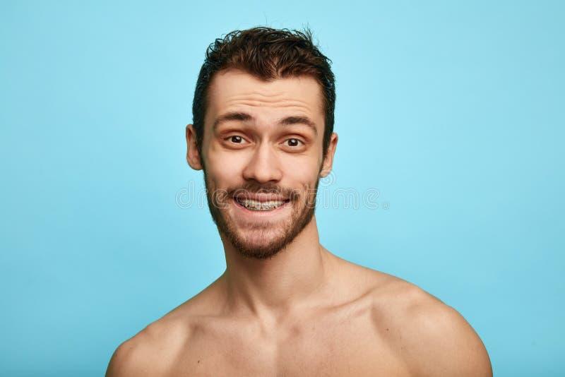 Foto da posi??o madura de sorriso do homem isolada sobre o fundo cinzento da parede despido olhando a c?mera imagem de stock