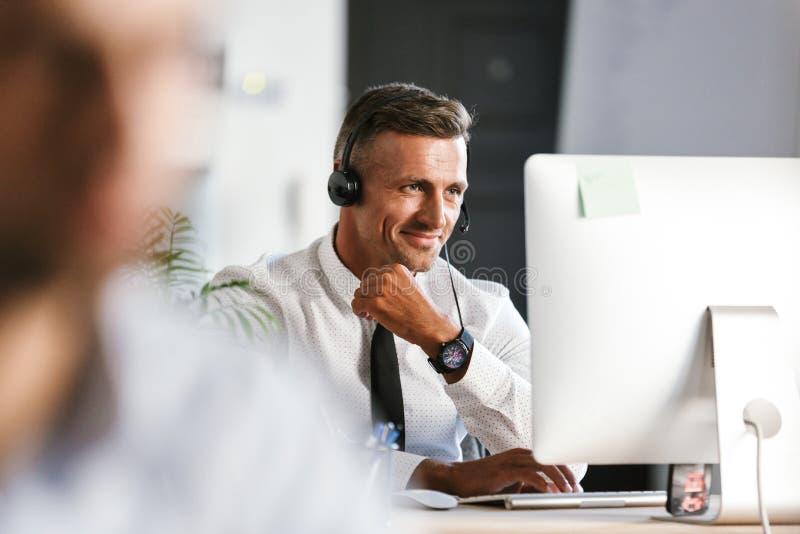 Foto da roupa do escritório do homem 30s e dos auriculares vestindo consideráveis, wo foto de stock royalty free