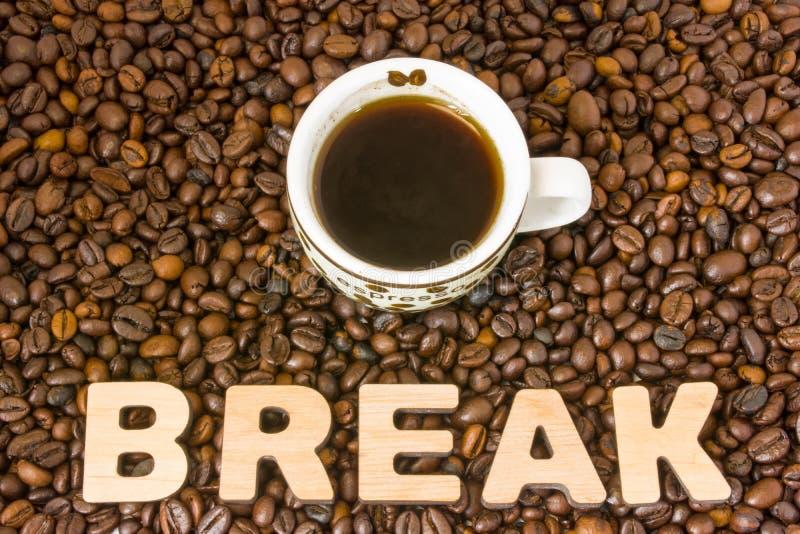 Foto da ruptura de café O copo com café fabricado cerveja está na tabela, que se encheu com os feijões de café roasted, ao lado d foto de stock