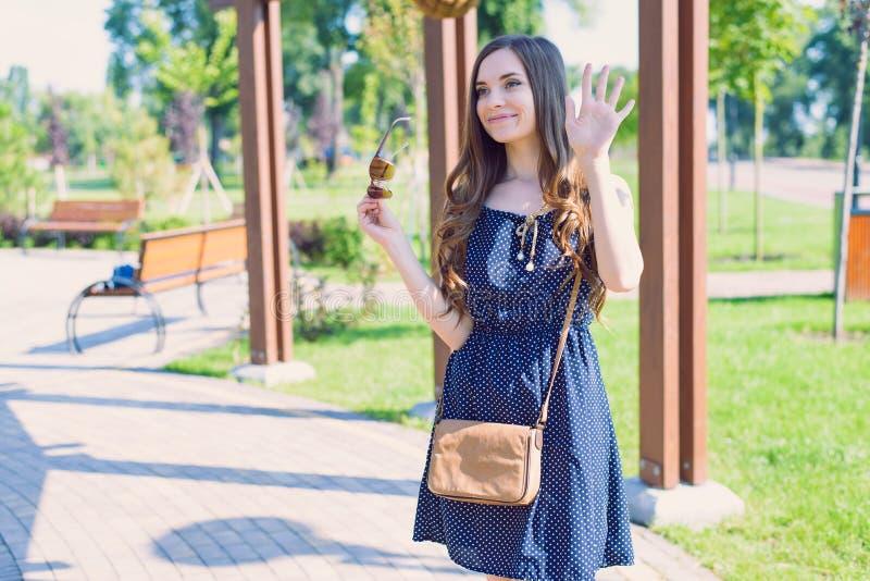 A foto da senhora agradável satisfeita doce que envia o adeus do provérbio do cumprimento ao azul vestindo da amiga pontilhou gua fotografia de stock