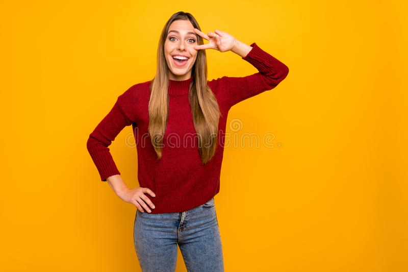 Foto da senhora bonita que mostra o v-sinal perto do fundo amarelo isolado pulôver do desgaste do olho imagens de stock