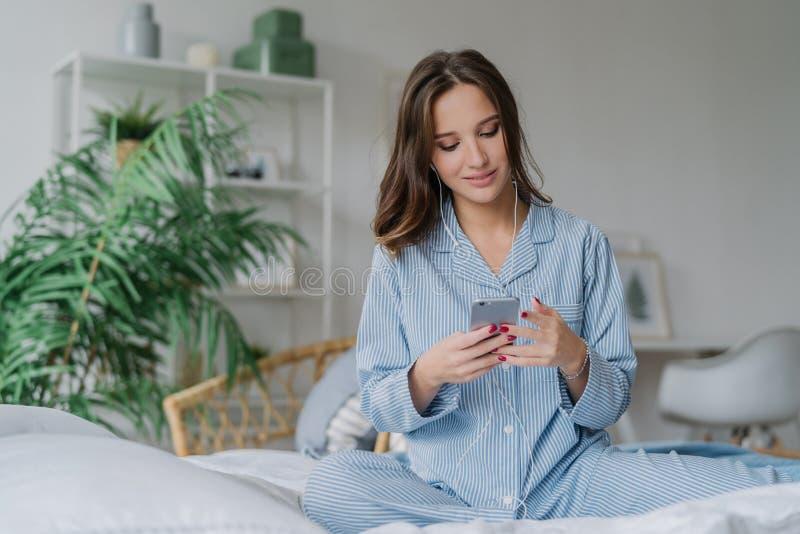 A foto da senhora europeia nova relaxado nos pyjamas aprecia a lista de músicas audio, escuta músicas românticas da música nos fo fotografia de stock