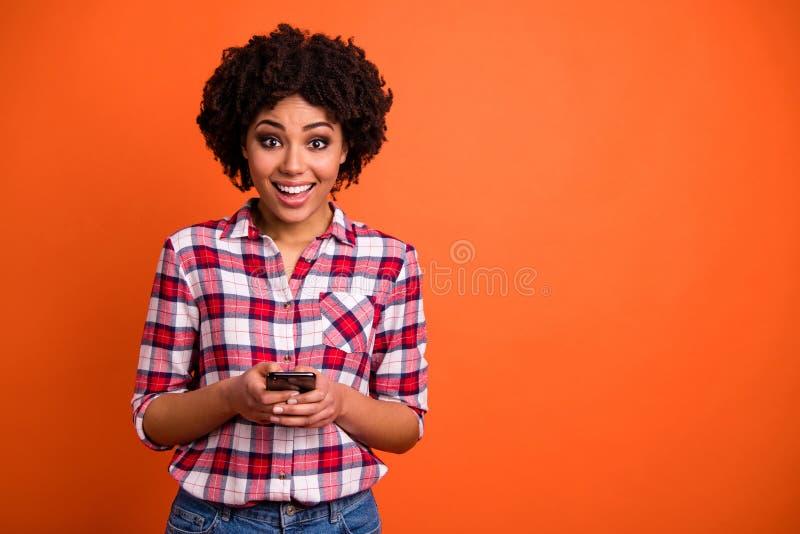 A foto da senhora surpreendida bonita engraçada guarda o telefone das mãos que escreve a desgaste do e-mail da letra a camisa de  foto de stock royalty free