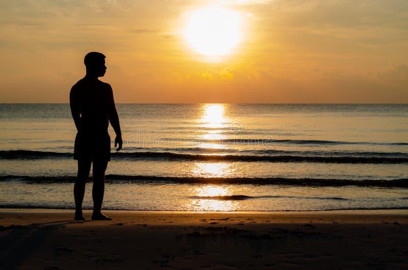 A foto da silhueta de um homem que est? apenas na praia aprecia o momento do nascer do sol foto de stock royalty free