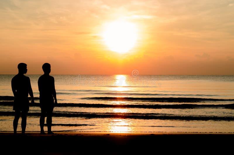 A foto da silhueta dos pares alegres que estão junto na praia imagem de stock royalty free