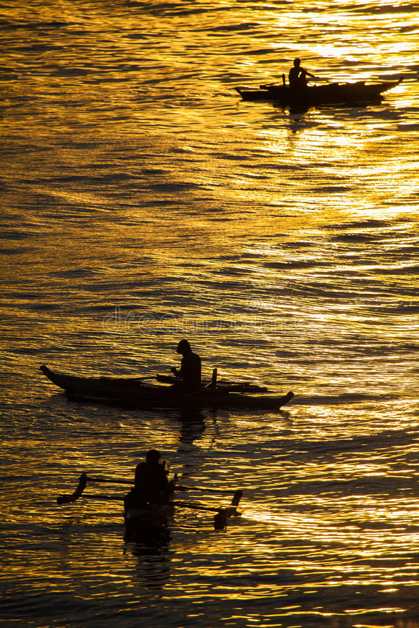 Foto da silhueta Peixes da captura dos pescadores no por do sol Sóis bonitos foto de stock