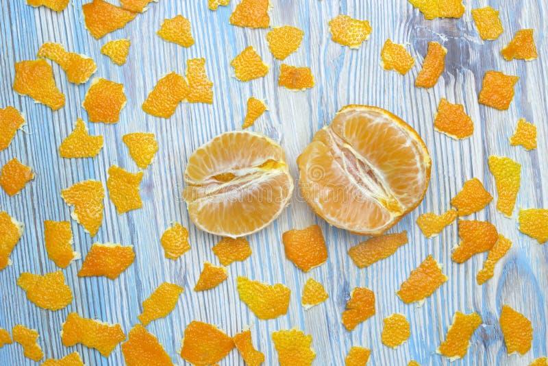Foto da sopra del mandarino sbucciato e molti pezzi di scorza d'arancia Due parti del mandarino succoso sbucciato della fetta fotografia stock libera da diritti