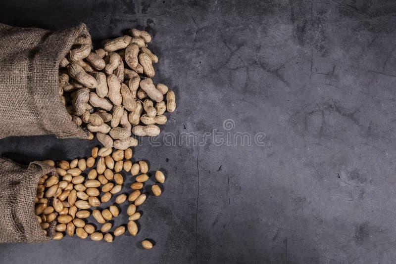 A foto da vista superior dos amendoins derramados, amendoins no saco do saco, alinhado à esquerda para o texto da cópia, fundo é  fotos de stock royalty free