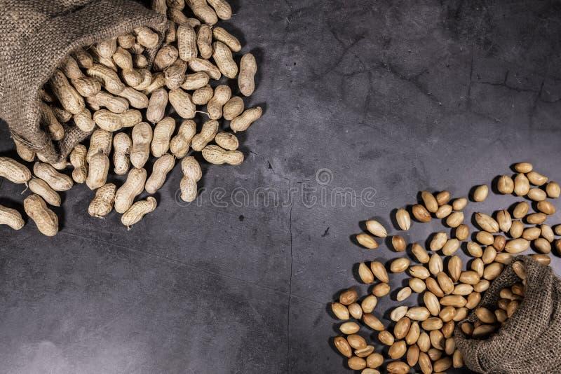 A foto da vista superior dos amendoins derramados, amendoins no saco do saco, alinhado à esquerda para o texto da cópia, fundo é  foto de stock