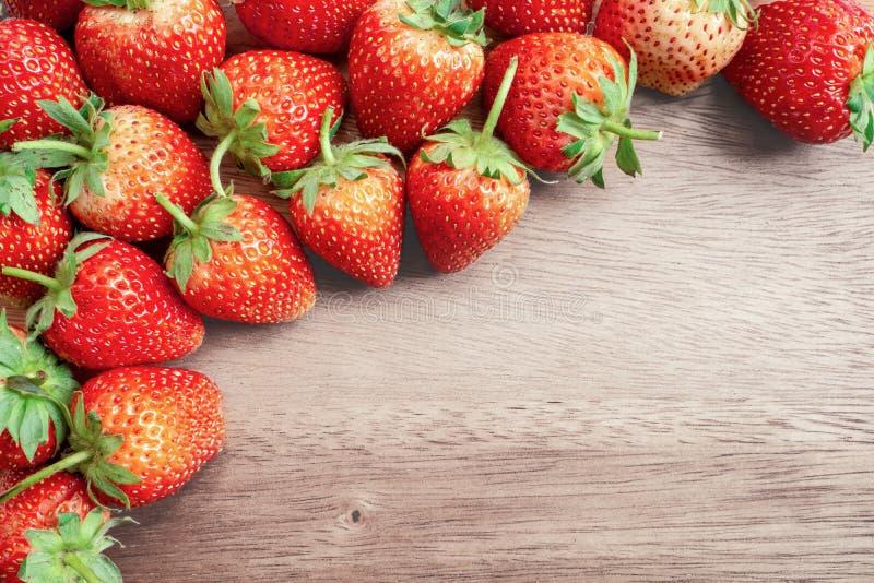 Foto da vista superior, um montão do fruto de baga fresco, morango vermelha no assoalho de madeira com espaço coppy fotografia de stock royalty free