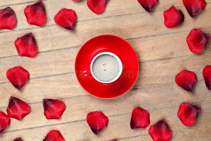 Foto da xícara de café e das pétalas cor-de-rosa secadas no maravilhoso foto de stock royalty free