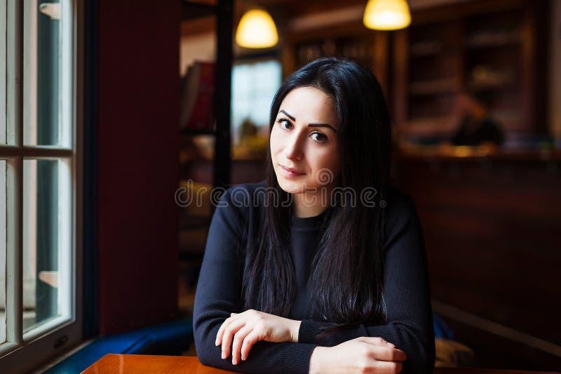 Foto das belas artes de uma mulher moreno lindo que senta-se apenas perto de uma janela e de uma espera fotografia de stock