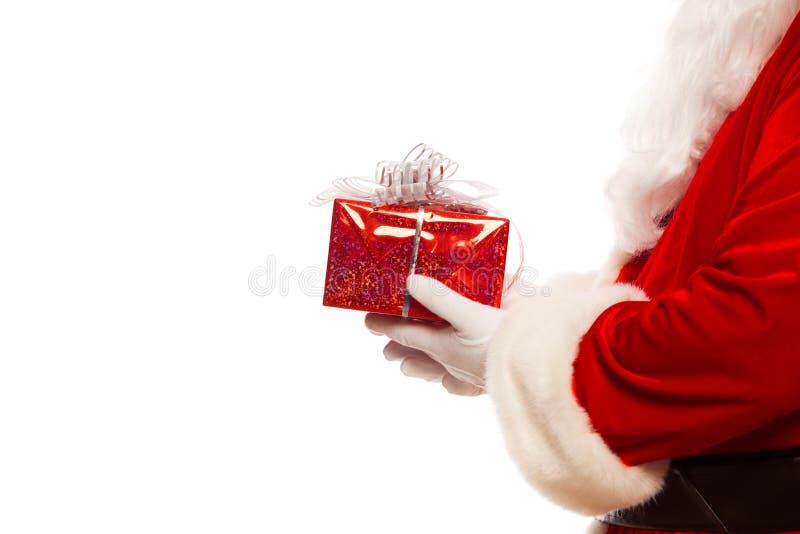 Foto das mãos gloved de Santa Claus que guardam o giftbox vermelho, isolada no Natal branco do fundo imagens de stock