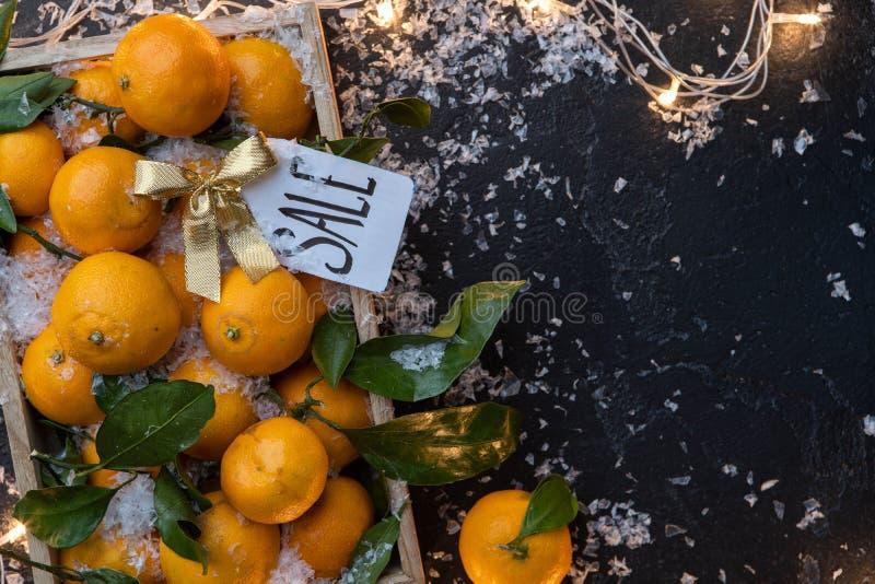 Foto das tangerinas na caixa de madeira, cartão na tabela preta imagem de stock royalty free