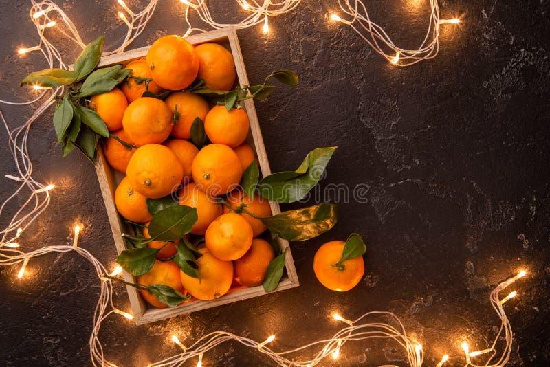 Foto das tangerinas na caixa de madeira com festão de queimadura imagens de stock royalty free