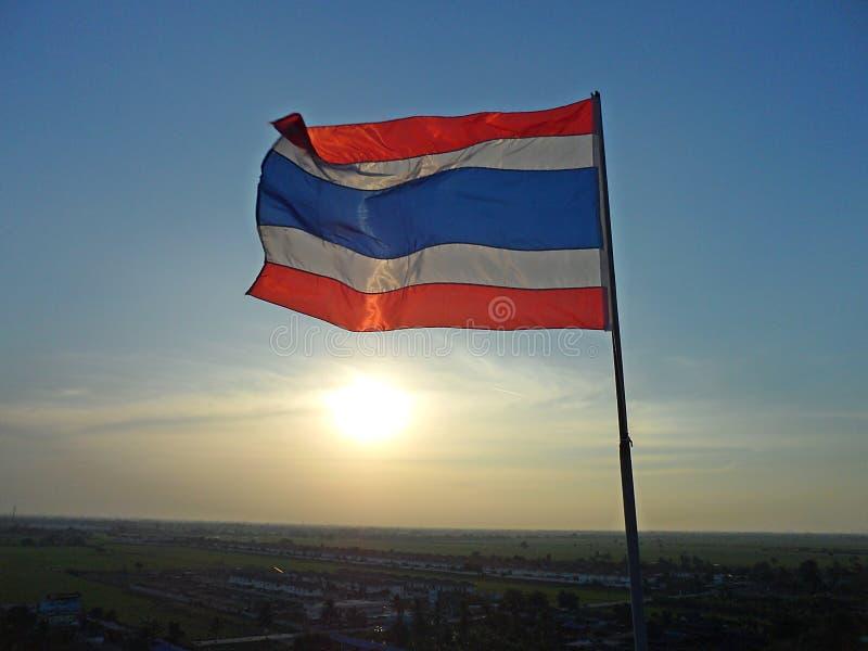 A foto de acenar a bandeira tailandesa de Tailândia com o sol brilha no fundo da noite fotografia de stock