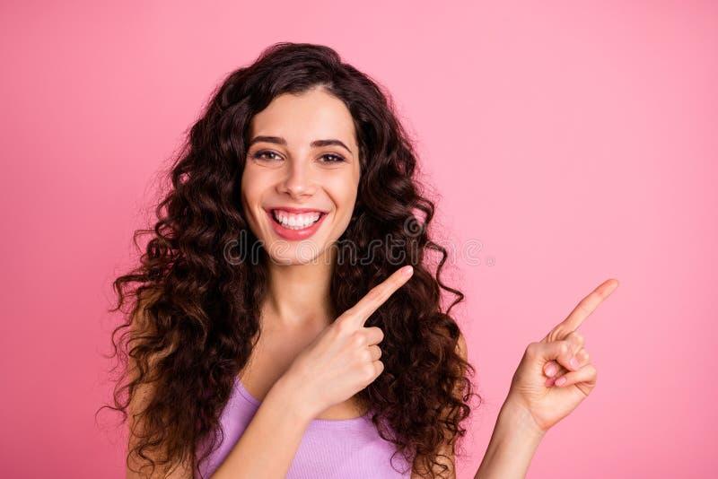 Foto de alegre y encantadora chica amable y agradable señalando tu mejor elección, aislada con rosa fotografía de archivo