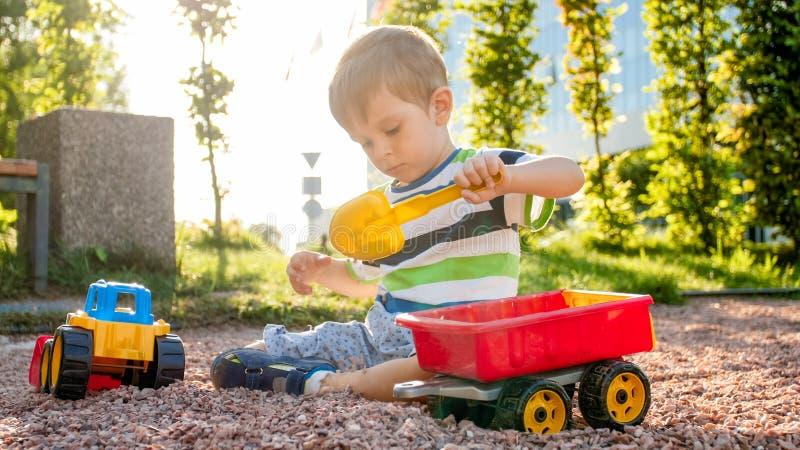 Foto de 3 anos adoráveis do menino idoso da criança que joga com areia e você caminhão e reboque no parque Criança que escava e foto de stock