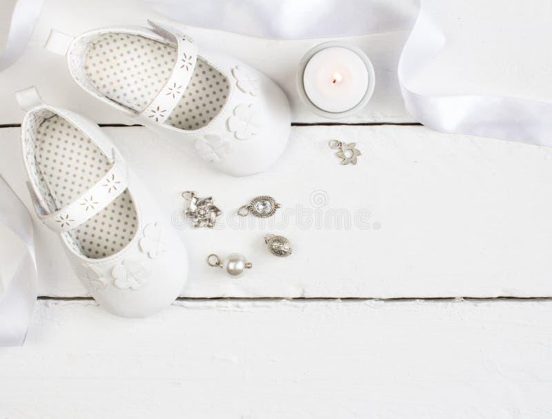 Foto de arriba de los pares de botines blancos del bebé, vela, cinta y foto de archivo libre de regalías
