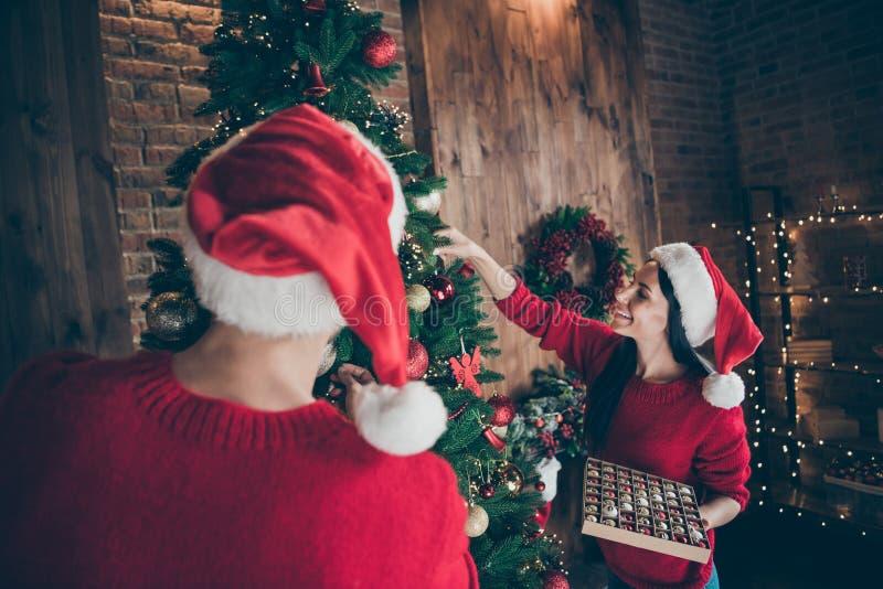Foto de atrás de dos personas románticas sosteniendo baubles decorando árboles de Navidad siempre verdes disfrutan de vacacione imagen de archivo libre de regalías