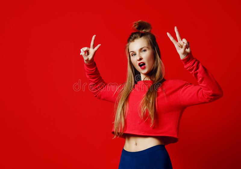 Foto de bonito, sorrindo, menina positiva que mostra o símbolo de paz, olhando a câmera, levantando no fundo colorido imagens de stock