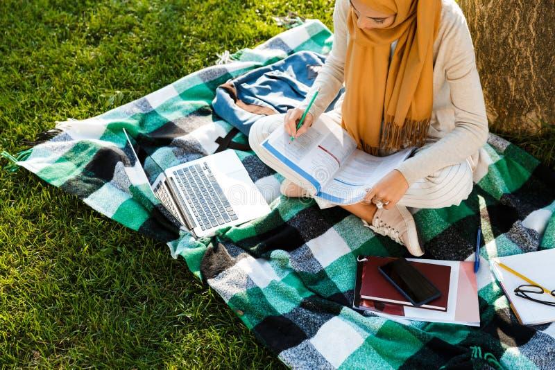 Foto de cima do assento vestindo árabe novo do lenço do estudante fêmea na cobertura imagem de stock