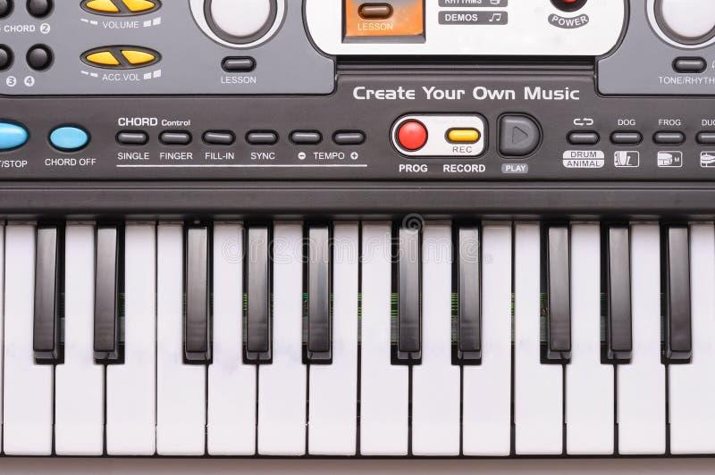 Foto de cima para baixo das teclas de um piano do teclado de brinquedo com os vários controles de som imagem de stock