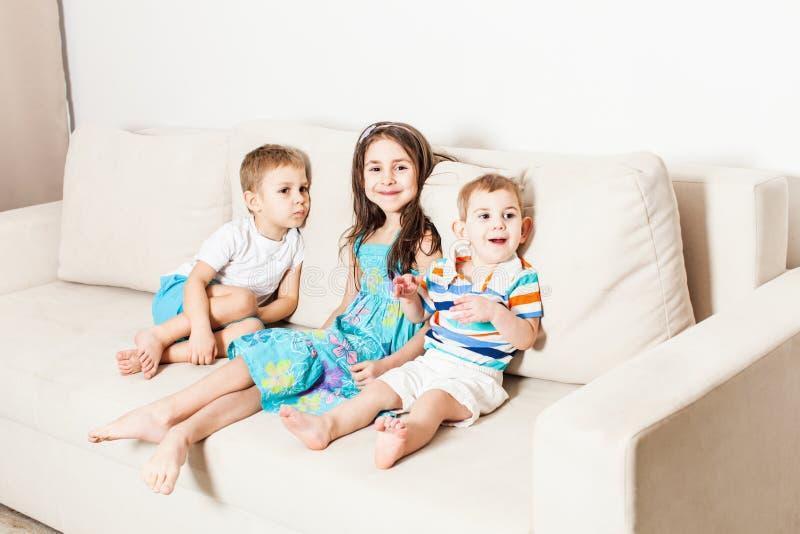 Foto de crianças bonitas no sofá moderno branco imagem de stock royalty free