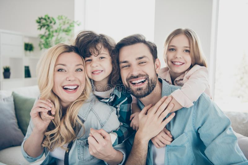 Foto de cuatro miembros de la familia después de la adopción que hace que el mejor júbilo del tiempo siente la sala de estar del  foto de archivo