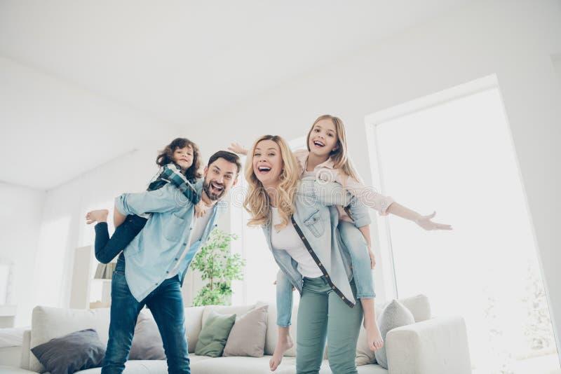 Foto de cuatro miembros de la familia que tienen mejores manos del tiempo libre como los apartamentos del vuelo del aeroplano de  fotos de archivo