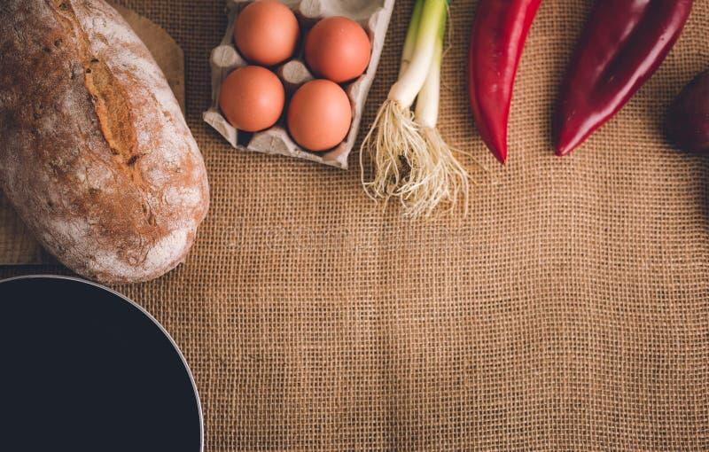 Foto de diversos verduras frescas, pan, huevos y cacerola en la tabla cubierta con el yute Foto de la comida y de los ingrediente imagenes de archivo