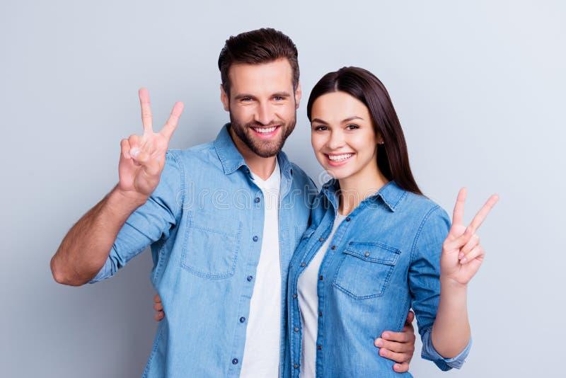 Foto de dos personas sonrientes felices jovenes en las camisas de los vaqueros aisladas imágenes de archivo libres de regalías