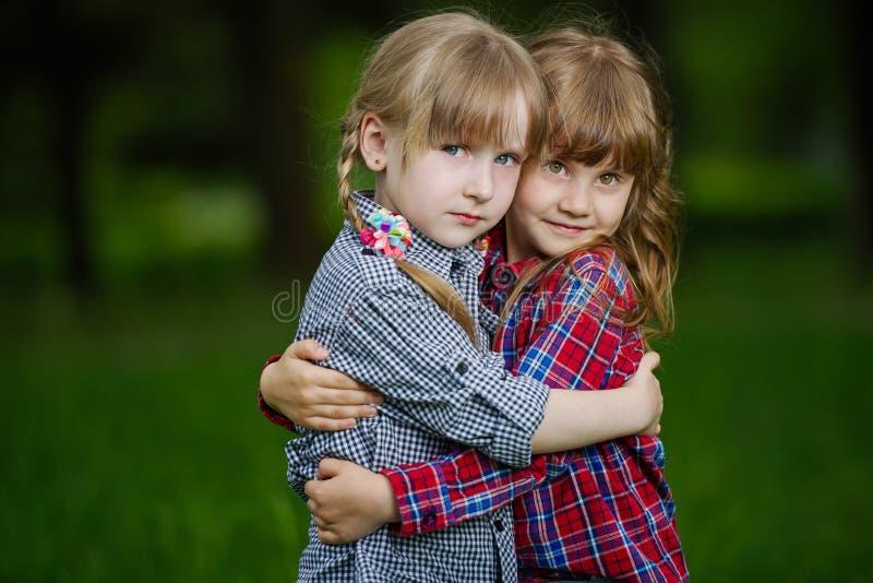 Foto de duas meninas de aperto felizes fotos de stock royalty free