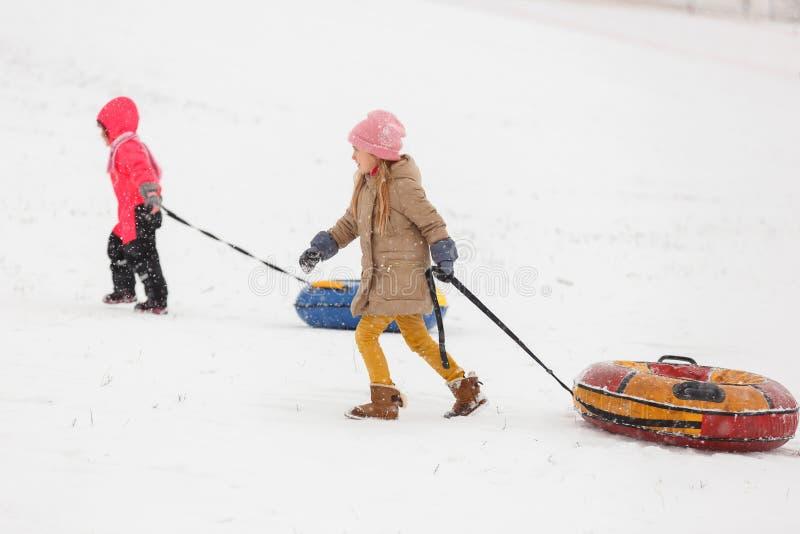 Foto de duas meninas na caminhada com tubulação no parque do inverno imagens de stock royalty free