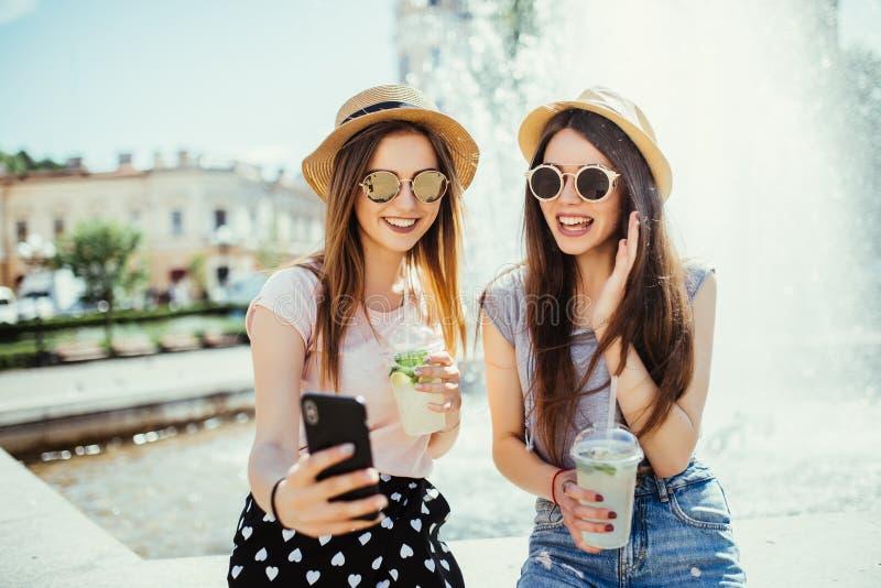 A foto de duas mulheres satisfeitos da raça misturada obtém boas notícias no telefone celular, recebe o e-mail ou para fazer o se foto de stock royalty free