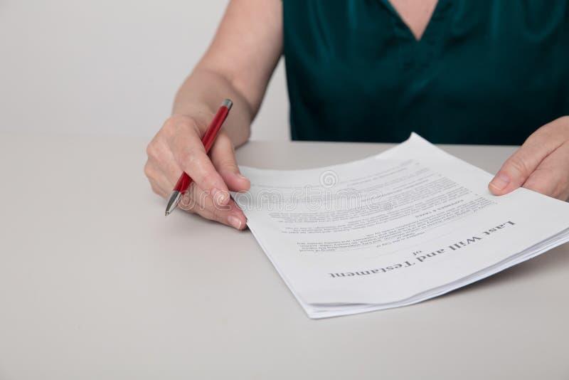 Foto de encerramento das mãos de uma mulher com documentos em papel e uma caneta sobre a mesa fotos de stock