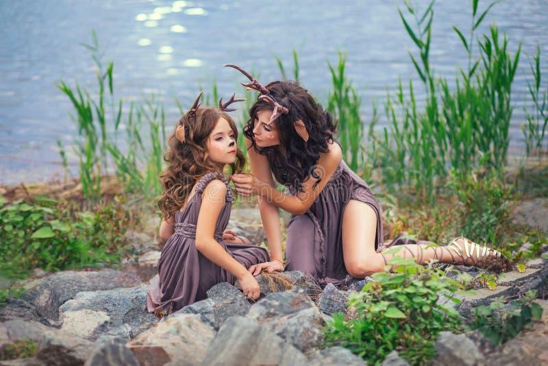 A foto de família da mãe e da criança, faunos na costa de um grande lago está sentando-se em pedras, caráteres do conto de fadas, imagens de stock