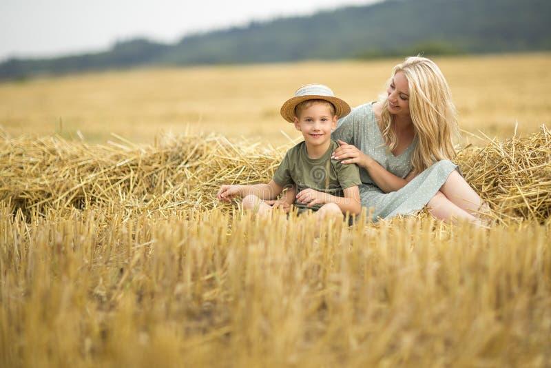 Foto de família: louro da mamã com cabelo longo em um chapéu e em um filho de palha que jogam no campo A família na vila Valores  fotografia de stock royalty free