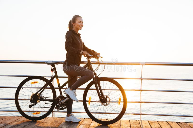 Foto de la bicicleta sana del montar a caballo de la mujer en paseo marítimo, durante salida del sol sobre el mar imagenes de archivo
