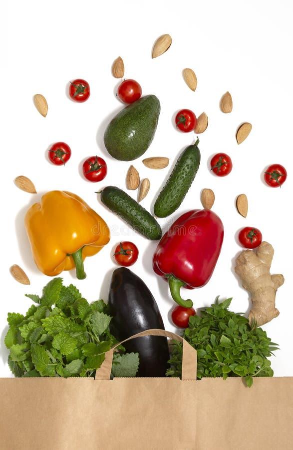 Foto de la bolsa de papel con las verduras y las frutas Composición plana de la endecha con las verduras frescas en el fondo blan foto de archivo