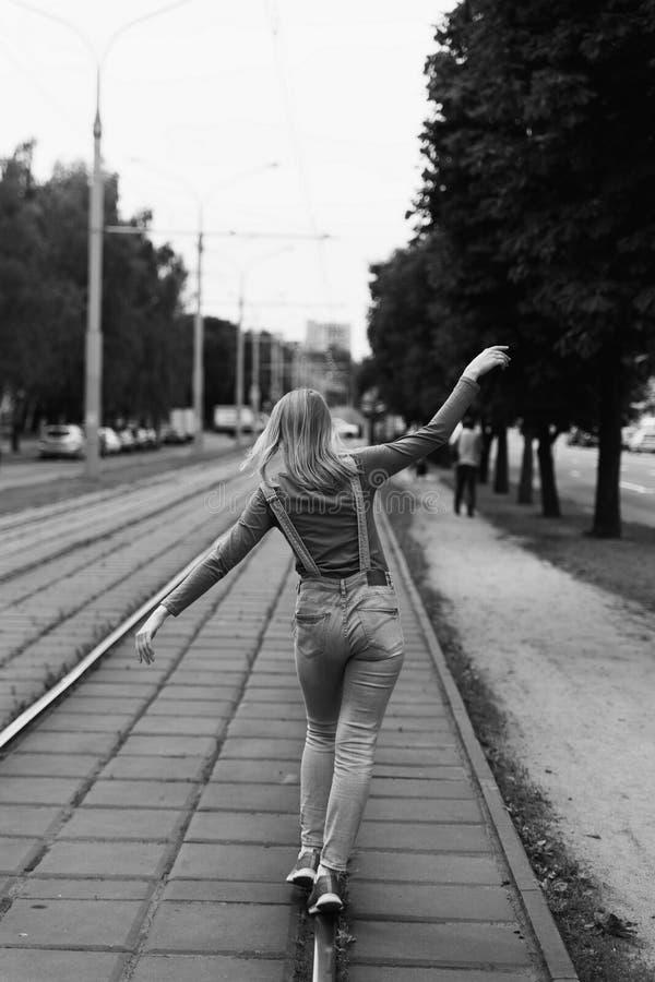 Foto de la calle en el estilo de una película blanco y negro vieja con el grano - una mujer está caminando a lo largo de los carr imagen de archivo
