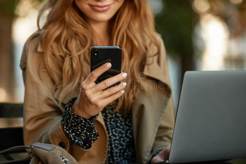 Foto de la empresaria que usa el teléfono móvil y el ordenador portátil mientras que se sienta en banco en callejón iluminado por fotos de archivo libres de regalías