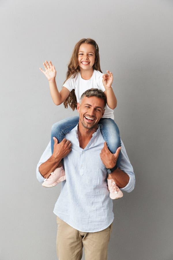 Foto de la familia alegre que sonríe en la cámara mientras que havin de la niña imagen de archivo