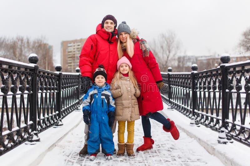 Foto de la familia con los niños en invierno en el puente foto de archivo libre de regalías