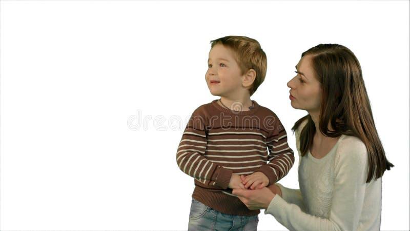 Foto de la familia joven feliz con los niños que miran para arriba en el fondo blanco aislado imagen de archivo libre de regalías