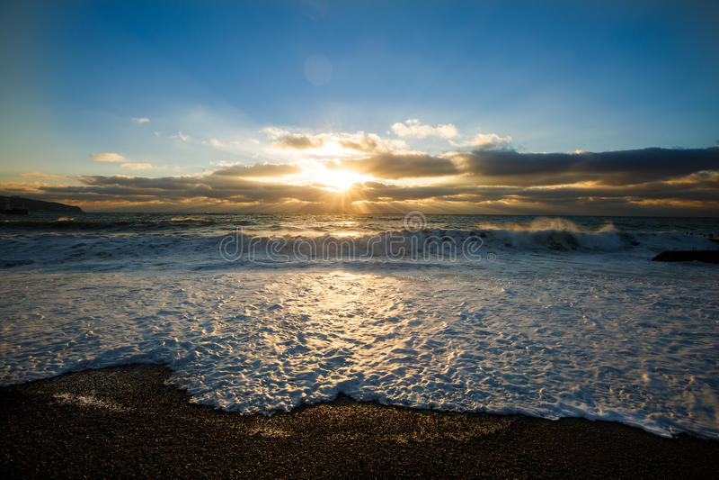 Foto de la mañana de una salida del sol sobre el mar tempestuoso en la playa y la espuma vacías de la arena del guijarro Cielo dr fotos de archivo libres de regalías