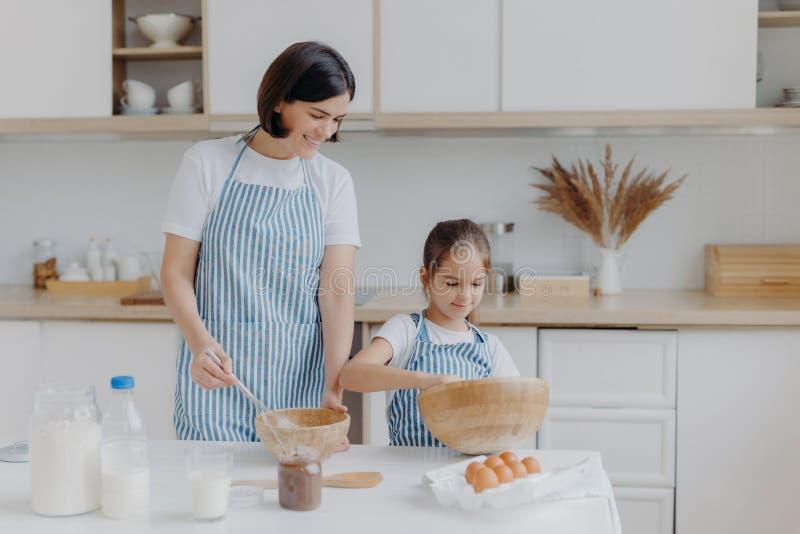 Foto de la madre de la morena y el niño pequeño hacen masa de galletas, ingredientes de whisky en tazón, vestidos en delantales,  fotografía de archivo libre de regalías