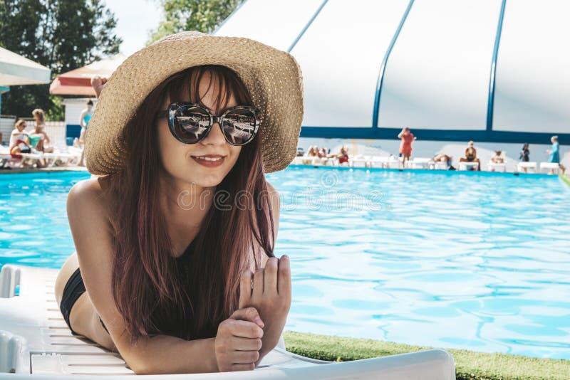 Foto de la moda de la muchacha hermosa atractiva en top negro y gafas de sol que relajan la mentira en un sillón blanco contra imágenes de archivo libres de regalías