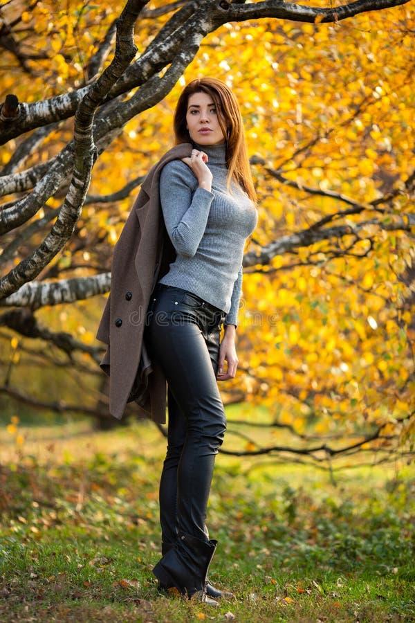 Foto de la morenita joven con la capa en su hombro en bosque del otoño foto de archivo libre de regalías