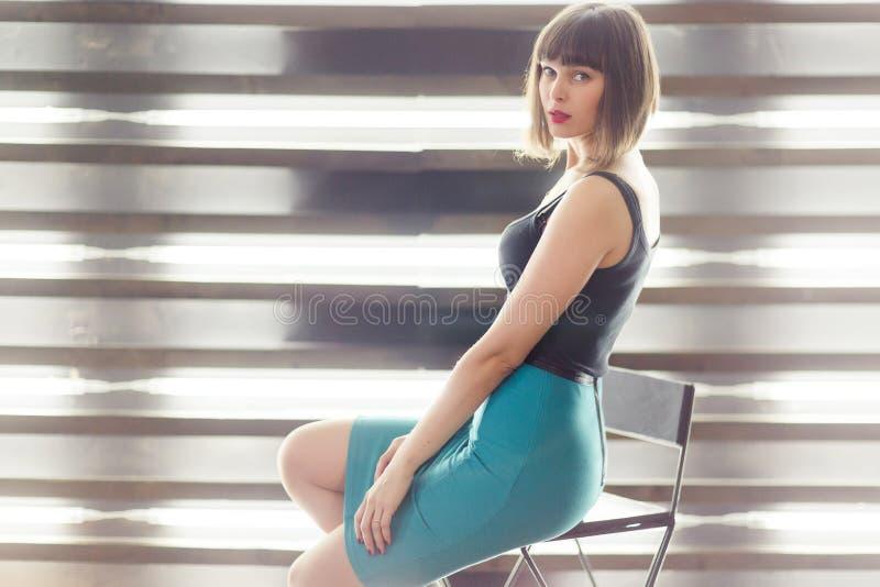 Foto de la morenita joven que se sienta en silla cerca de ventana con las persianas fotografía de archivo libre de regalías